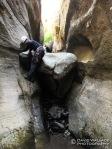 John down climbs past a choke stone.