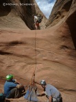 Brian (left) and David put sand in the Sandtrap anchor as A.J. gets ready to rappel.