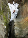 Eric stands atop a huge snow and ice patch at the bottom of a rappel.