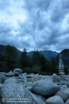 A cairn tower along the Maggia River as clouds roll in at dusk.