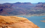 Adam is seen on a sandstone ridgeline in front of Lake Powell on the approach to Paradiso Canyon.