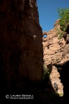 Wyatt and David hike under an arch in Deer Creek, a side canyon of Aravaipa Canyon.