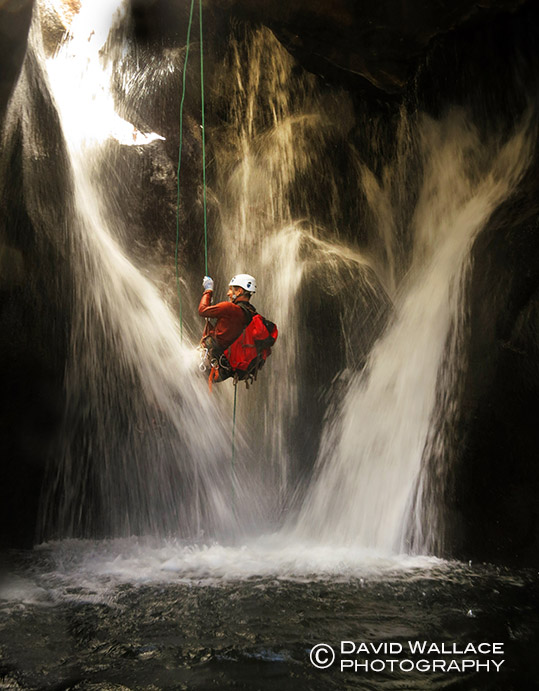Cody rappels through a three ribboned waterfall.
