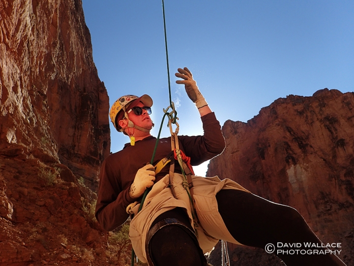 Steam rises from Chris' rappel device after touching it with his sweaty glove at the bottom of a 150 foot rappel in Tatahoysa Canyon in the Grand Canyon.