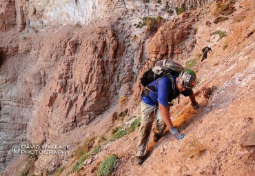 Brian traverses choosy rock during the approach to Whispering Falls Canyon.